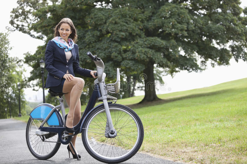 Young businessman riding bicycle while commuting to work stock photo
