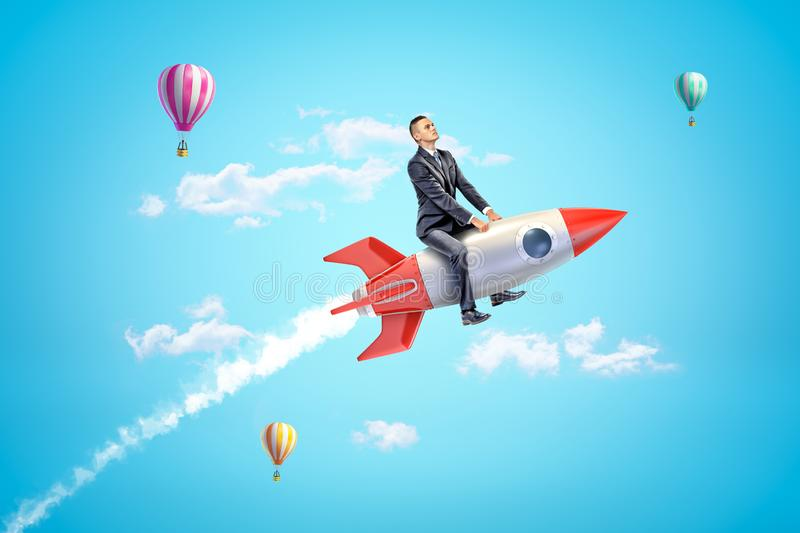 Young businessman riding toy rocket in blue sky with hot air balloons in background. Nothing is impossible. Successful career move. Investment in space stock photo