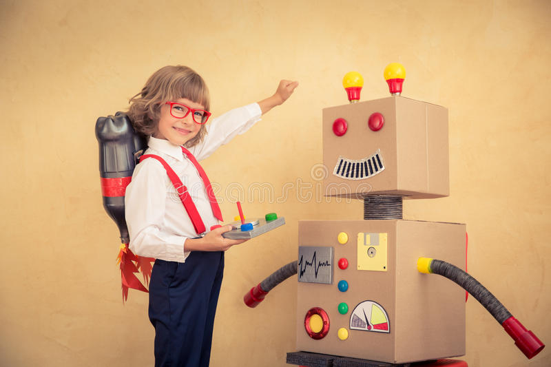Young businessman with robot. Portrait of young businessman with toy robot in modern loft office. Success, creative and innovation technology concept. Copy space stock photos
