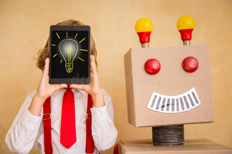 Young businessman with robot. Portrait of young businessman with toy robot in modern loft office. Success, creative and innovation technology concept. Copy space stock photography