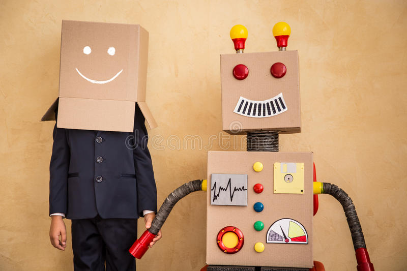 Young businessman with robot. Portrait of young businessman with toy robot in modern loft office. Success, creative and innovation technology concept. Copy space royalty free stock photos