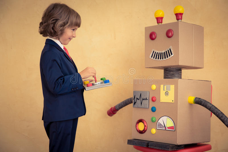 Young businessman with robot. Portrait of young businessman with toy robot in modern loft office. Success, creative and innovation technology concept. Copy space royalty free stock images