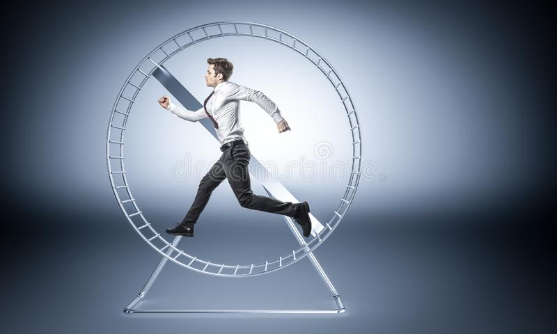 Work make me slave. Young businessman run in huge hamster wheele royalty free stock images