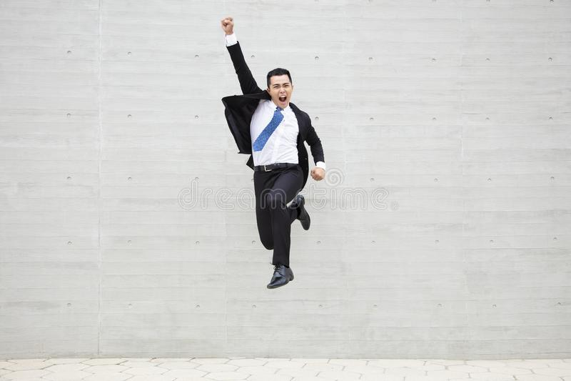 Young businessman running and jumping stock image