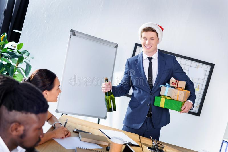 Businessman presenting gifts to colleagues. Young businessman in santa hat holding bottle of champagne and presenting gifts to happy colleagues in office stock image