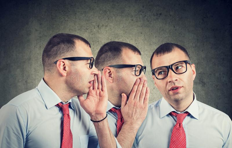 Young businessman self whispering in the ear royalty free stock photography