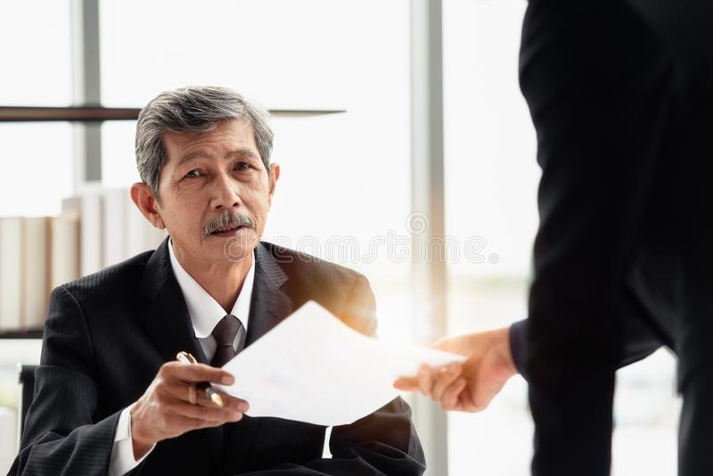 The businessman sending report to boss on hand. The young businessman sending the report to his boss on hand in the office room stock photography