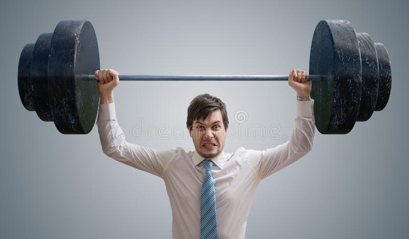 Young businessman in shirt is lifting heavy weights.  stock photography