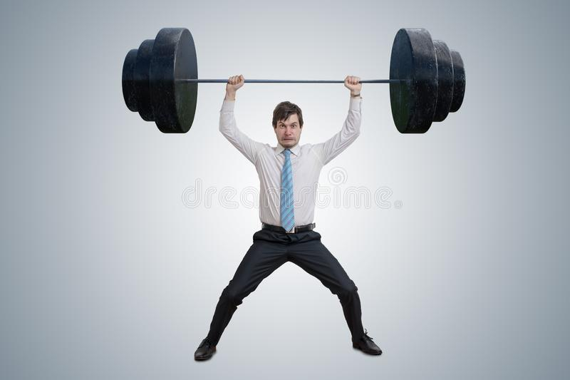 Young businessman in shirt is lifting heavy weights. Young businessman in shirt is lifting heavy weights royalty free stock images