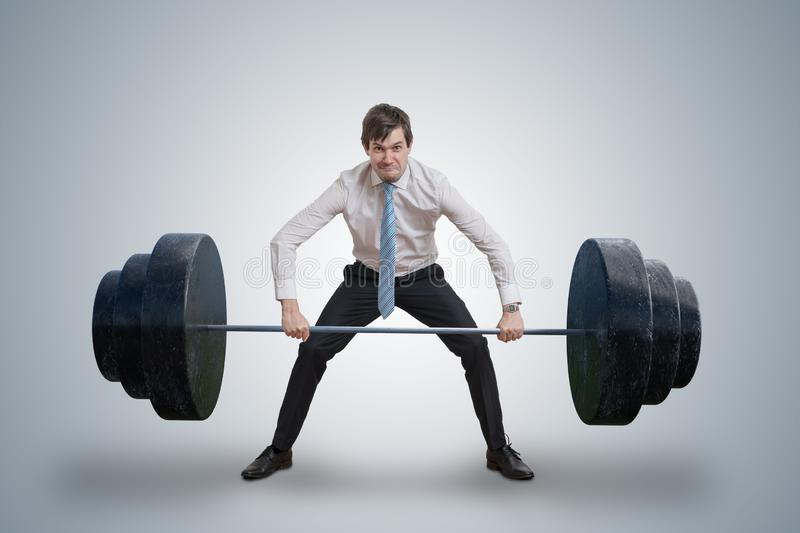 Young businessman in shirt is lifting heavy weights. stock photos