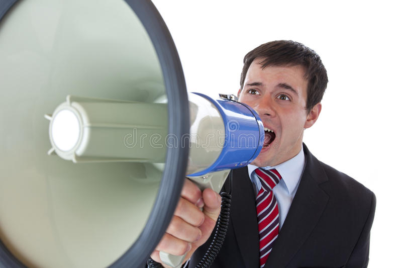Young businessman shouting loudly into megaphone stock photo