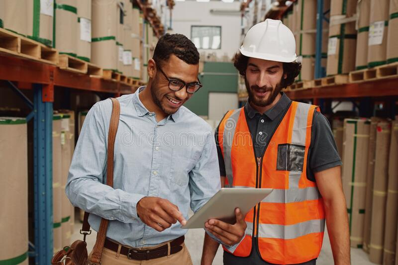 Young businessman showing data in touchpad to warehouse worker wearing hardhat and orange jacket uniform royalty free stock image