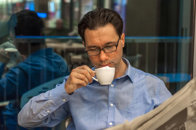 Young businessman sipping coffee and reading newspaper at cafe. Male business man, modern office building with beautiful light as background. Businessman stock images