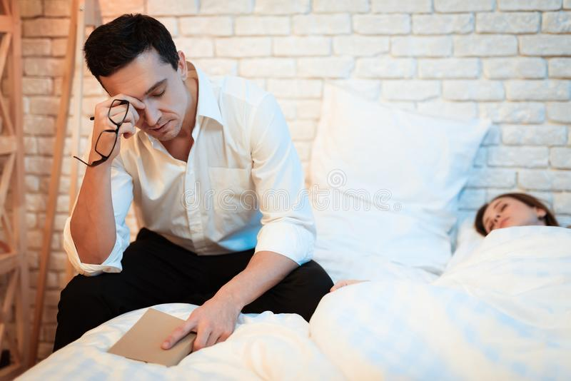 Young businessman sits on bed next to white woman and reads book. Businessman rubs tired eyes. royalty free stock photos