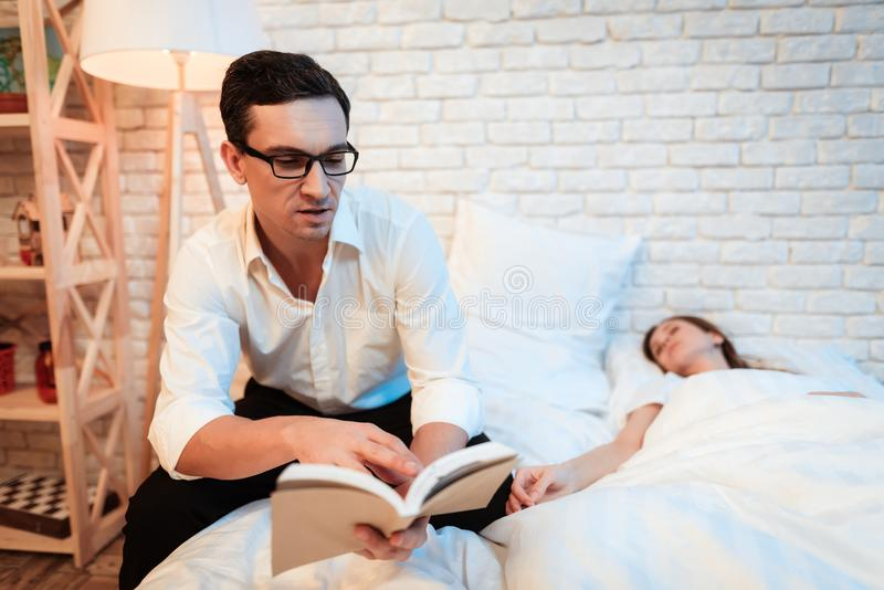 Young businessman sits on bed next to young woman and reads book. Woman is asleep. royalty free stock image