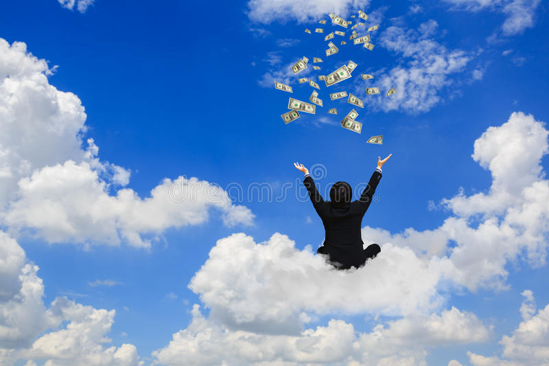 Young businessman sitting on the cloud with a lot of falling dollars stock photo