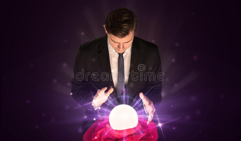 Businessman sitting with crystal ball in action stock photography