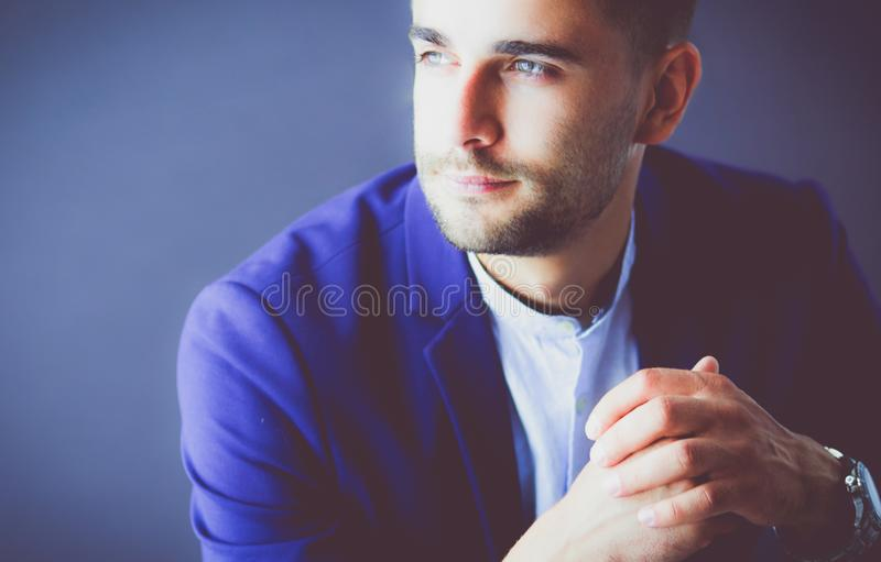 Young businessman sitting isolated on grey background stock image