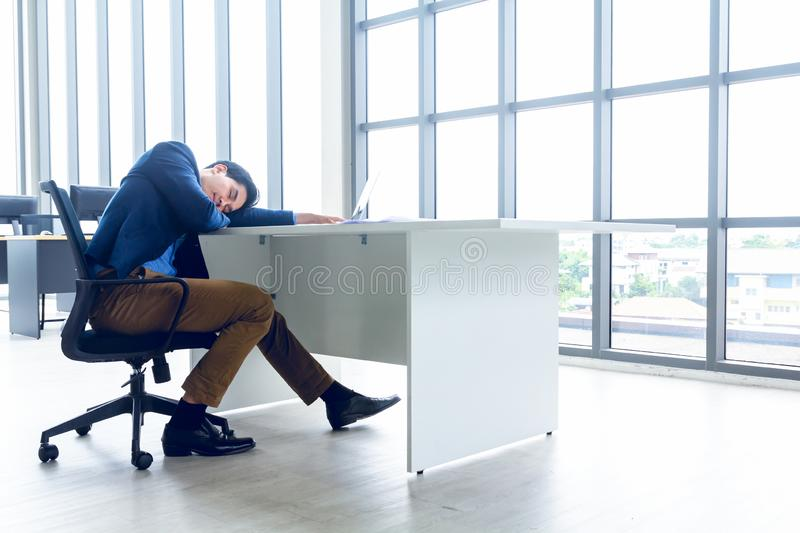 A young businessman sitting in a modern office. He has a feel sleepy because  hard work so tired weary fatigued and exhausted. On royalty free stock photography