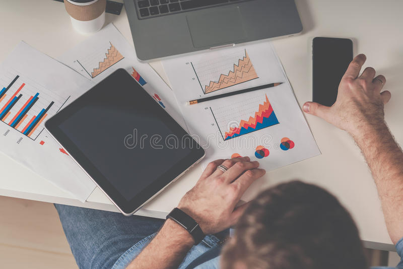Young businessman is sitting at office at table and working.On desk is laptop,tablet computer with blank screen royalty free stock photography