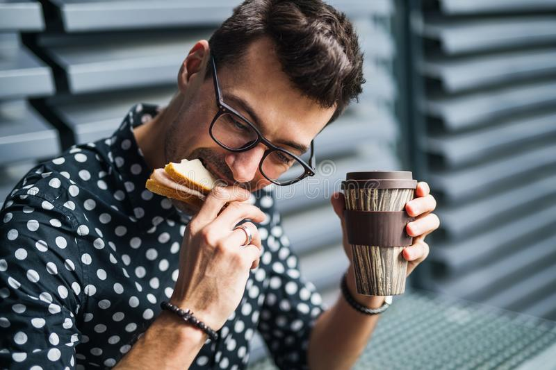 Young businessman sitting outdoors, drinking coffee and eating sandwich. royalty free stock photos