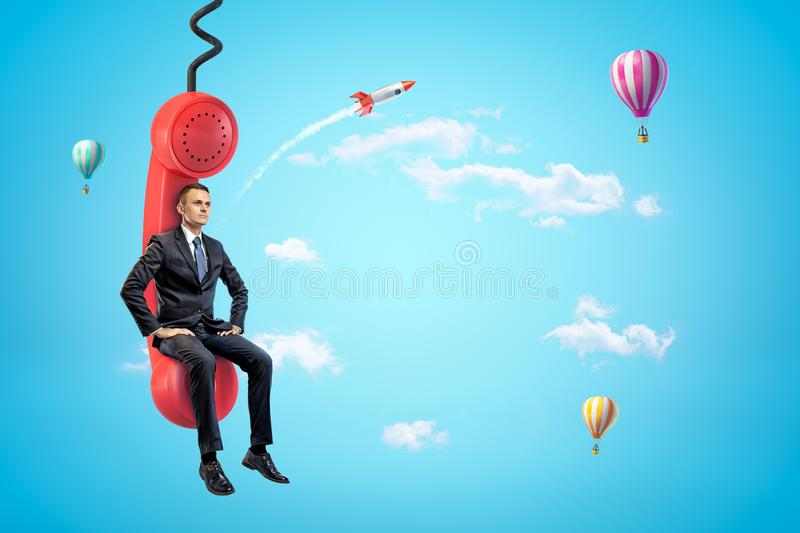 Young businessman sitting on red phone receiver in blue sky with hot air balloons and rocket in background. Business and finance. Business negotiation stock photo