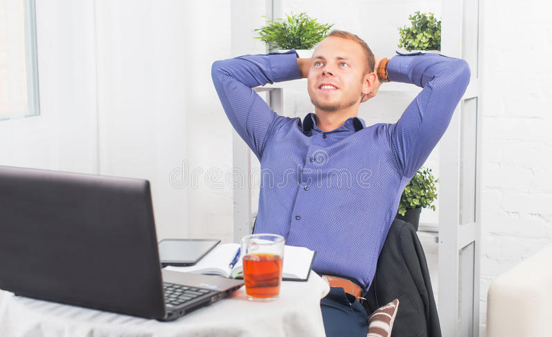 Young businessman sitting relaxed with hands behind his head, dreaming, thinking or resting. stock photo