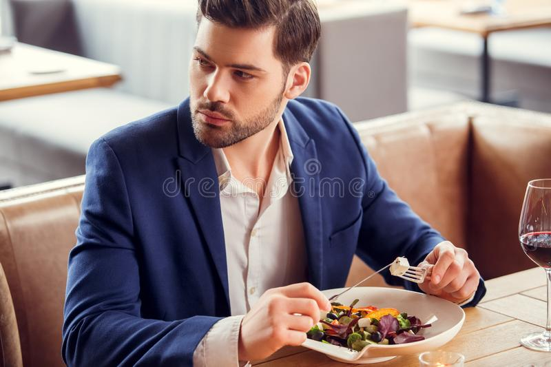 Young businessman sitting in restaurant eating salad drinking wine looking aside thoughtful stock photography