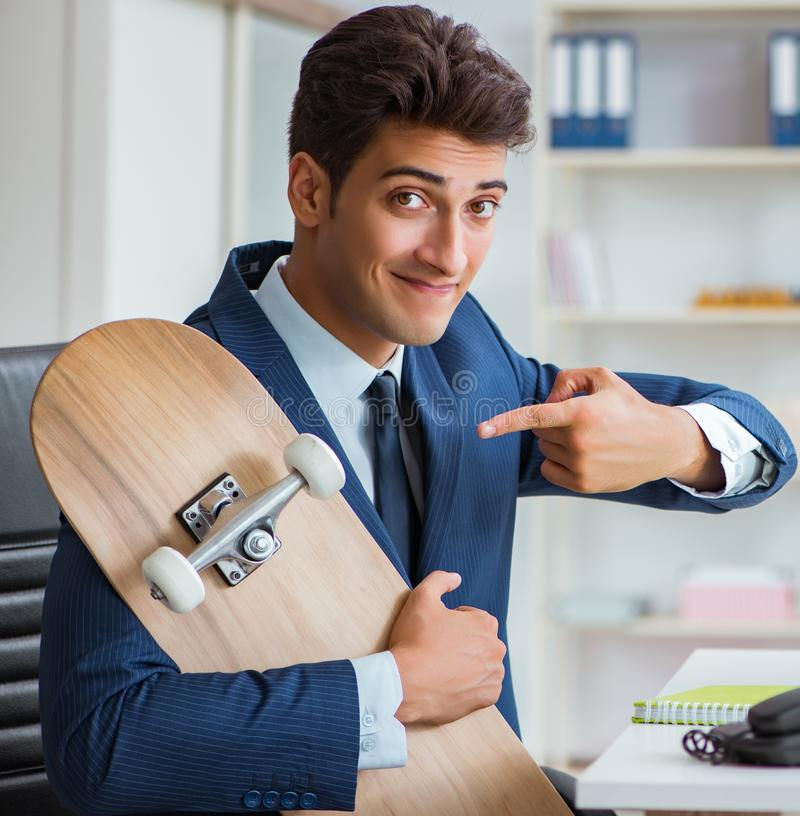 Young businessman with skate in office in sports concept. The young businessman with skate in office in sports concept stock photography