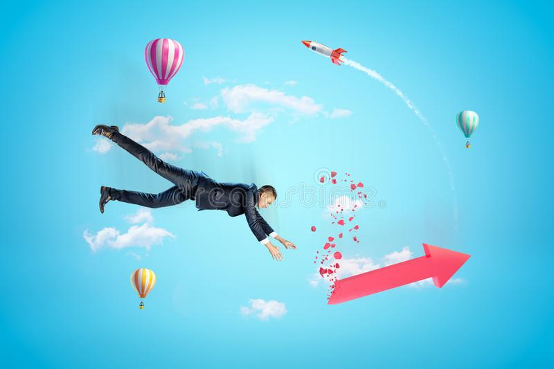 Young businessman in sky falling down trying to catch red broken graph arrow, with hot air balloons and rocket in. Background. Investment in ideas. Banking and stock photo