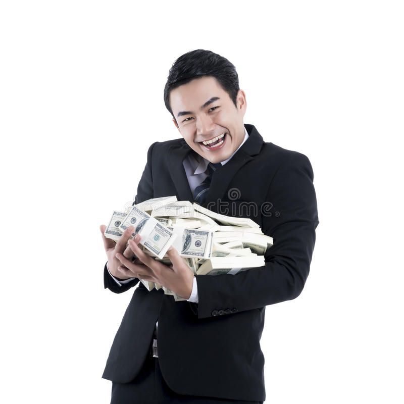 The young businessman smiling and holding a big pile of dollars royalty free stock photo