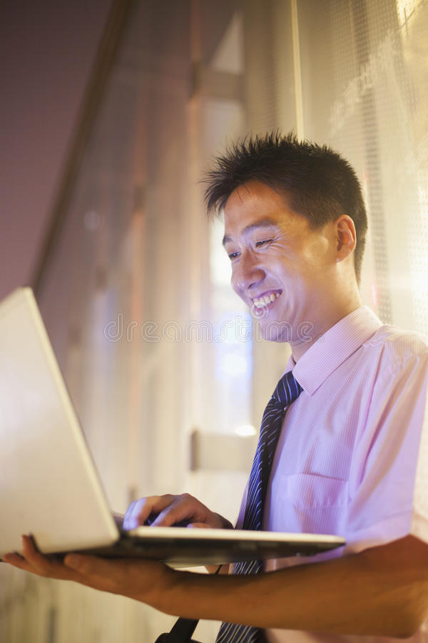 Young Businessman Smiling And Looking At His Laptop Outdoors At Night Stock Images