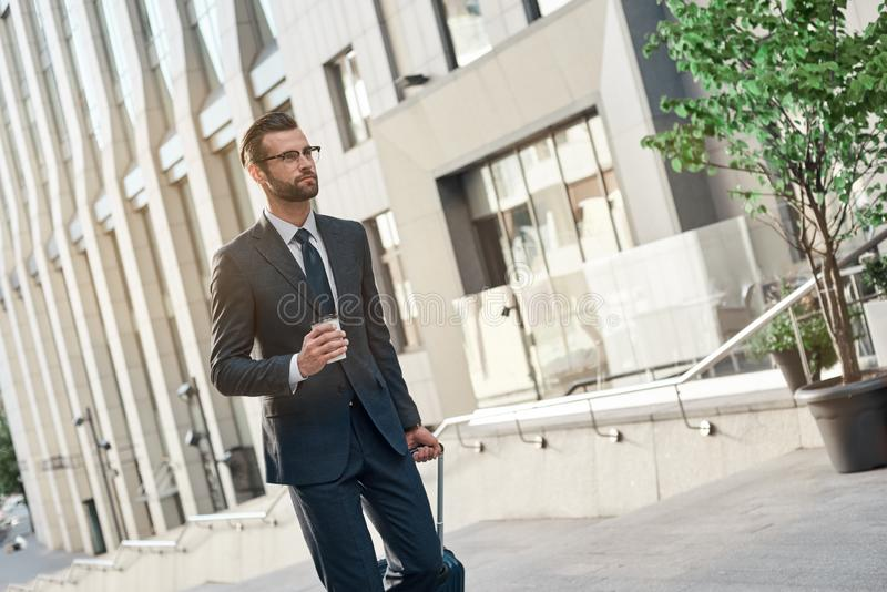 A young businessman spectacled climbs the stairs with coffe and suitcase royalty free stock image