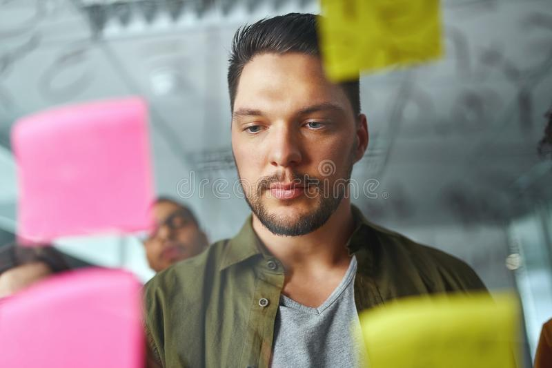 Portrait of a young businessman in casualwear standing behind the transparent glass looking at sticky notes at office stock images