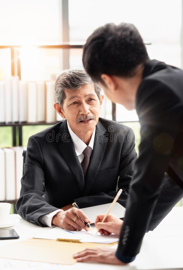 Young businessman standing discussing with boss. The young businessman standing and reporting the document discussing with his boss on the desk in his office stock images