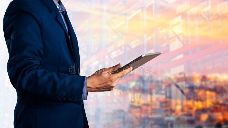 Young businessman standing and holding a tablet with the shipping royalty free stock images