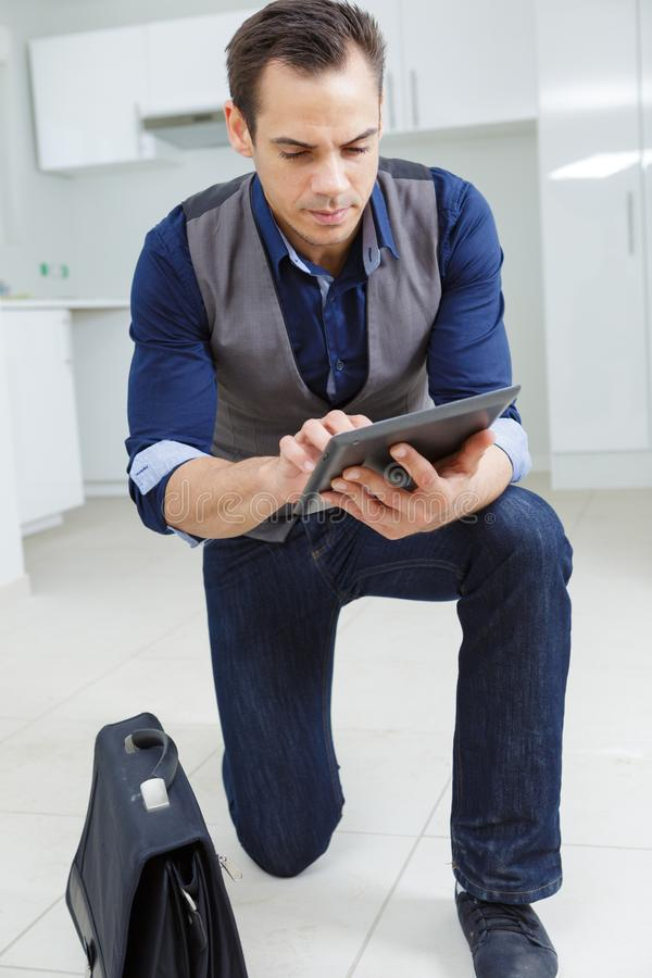 Young businessman standing indoors with tablet royalty free stock photography