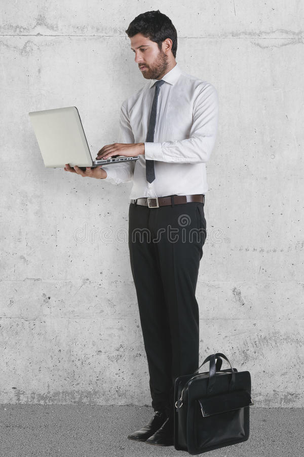 Young Businessman Standing With Laptop And Briefcase. Stock Photo