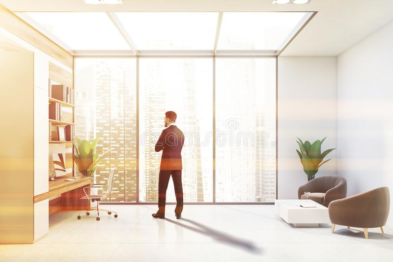 Man in white and wooden office with lounge stock photos