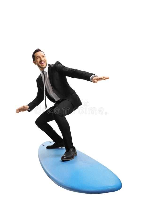 Young businessman standing on a surfing board. Full length shot of a young businessman standing on a surfing board isolated on white background royalty free stock photos