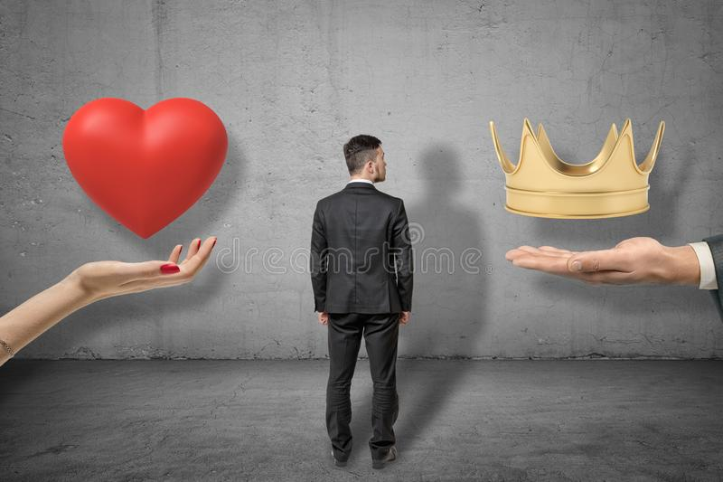 Young businessman standing between two big hands holding red heart and golden crown on grey wall background. background royalty free stock images