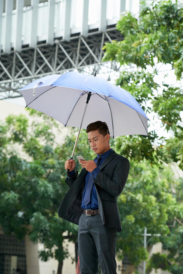 Young Businessman Standing with Umbrella in Street royalty free stock photo