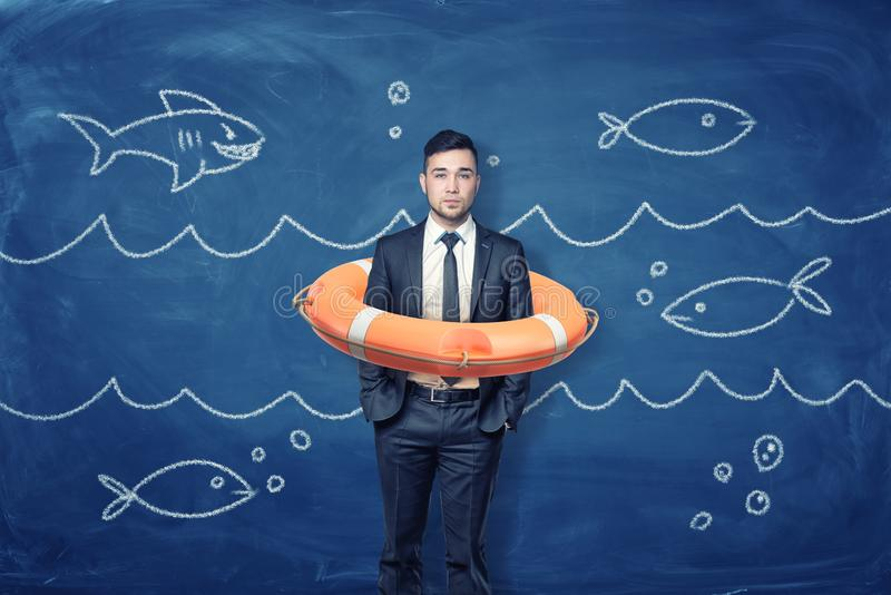A young businessman stands inside an orange life buoy on a blue background with chalk waves and fish. royalty free stock photography