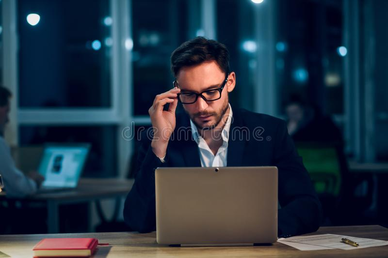 Young businessman staying up late working. stock image