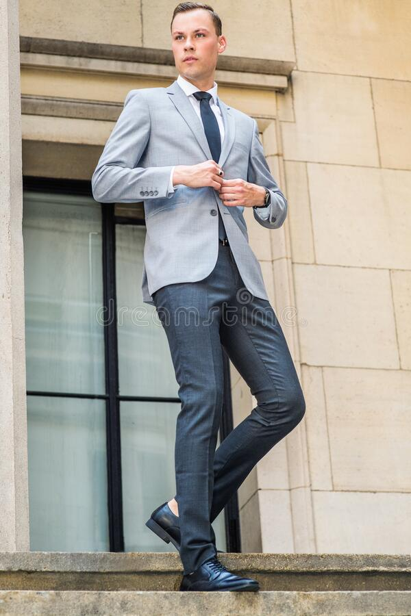 Young Businessman Street Fashion in New York City. Young Man wearing gray blazer, white shirt, tie, black pants, leather shoes, hands buttoning, walking down stock photos