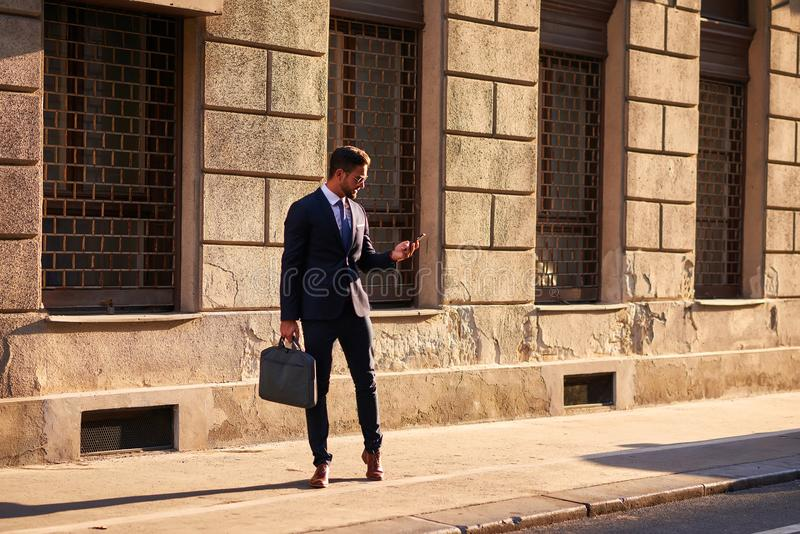 Young businessman on the street. A handsome young businessman walking on the street in the sunsetr stock photography