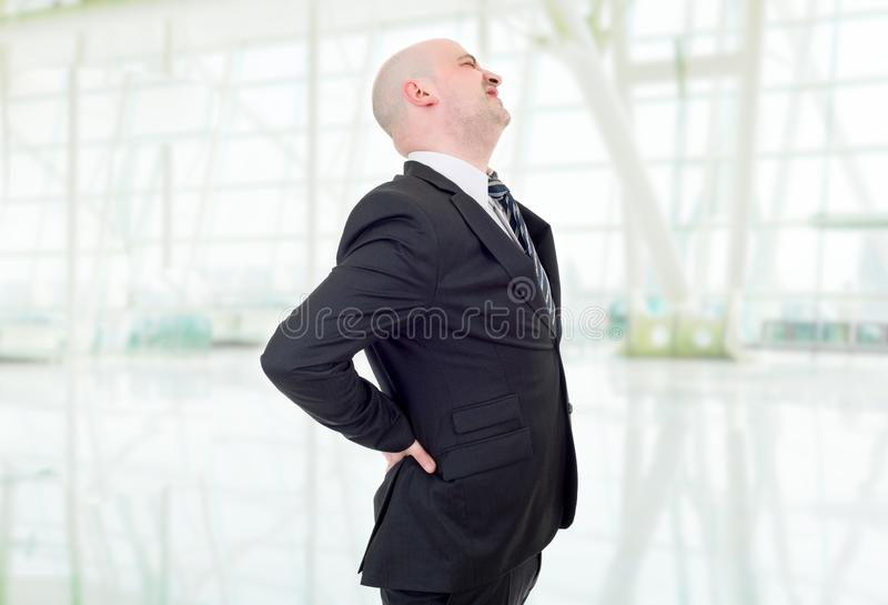 Businessman with strong back pain, at the office. Young businessman with strong back pain, at the office royalty free stock photo