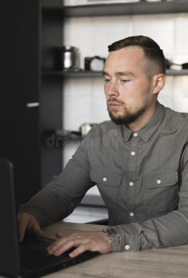 Young businessman or student in a shirt sitting against monitor of computer. Working on a pc at a table in the office stock photography