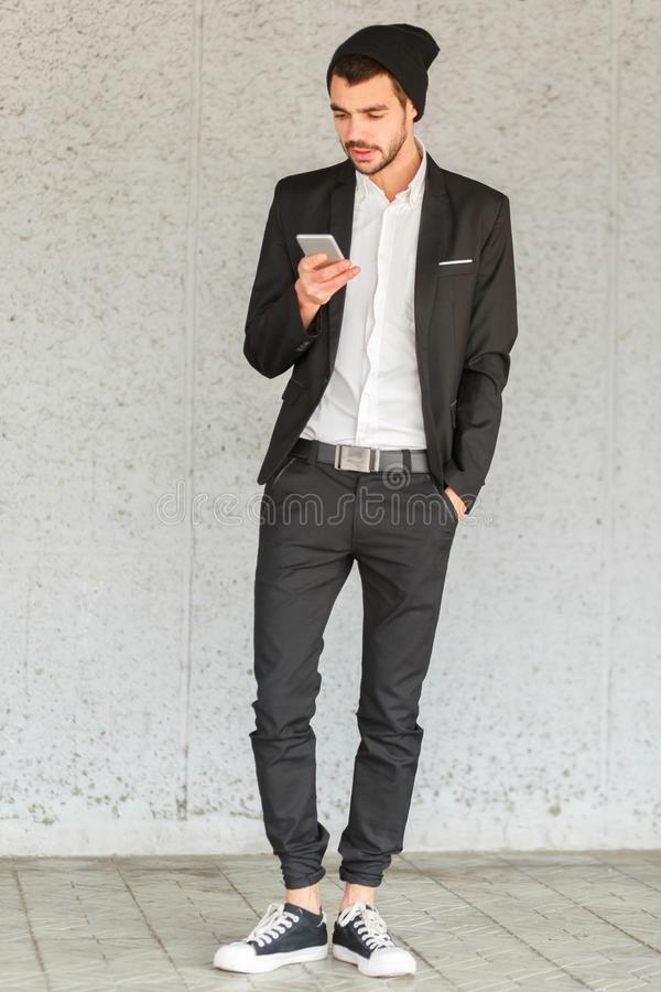 Young businessman stands by the wall and looks into the phone stock images