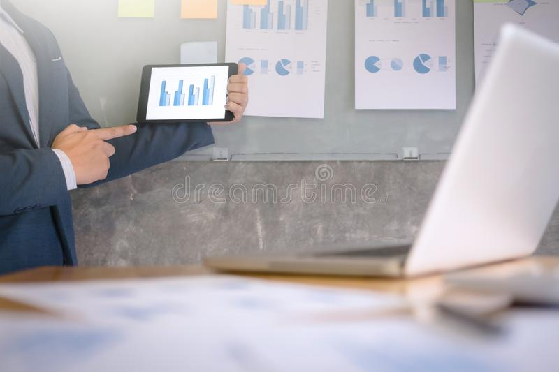 Young businessman in the suit explaining data chart on digital tablet and documents on the wall in a office.  stock image